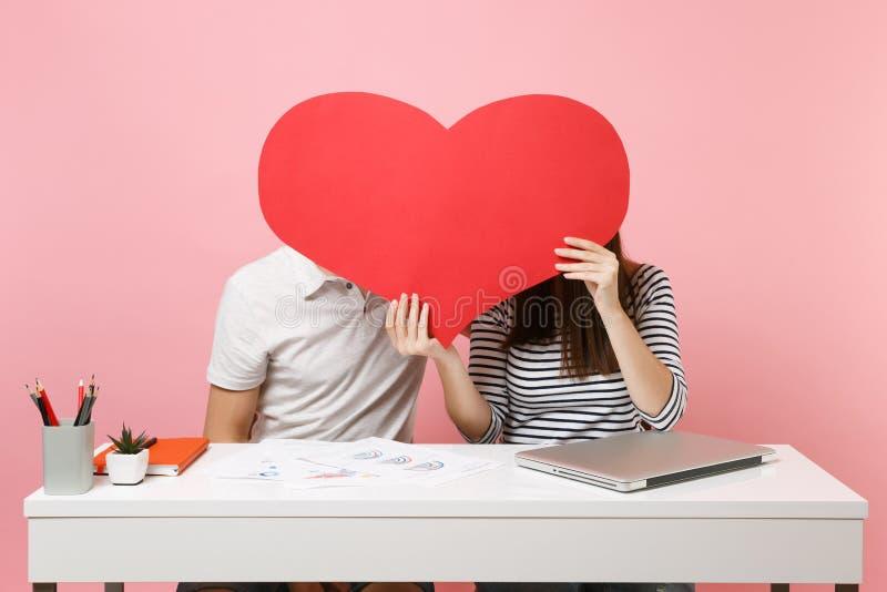 Dwa uśmiechniętego biznesowej kobiety mężczyzny kolegi siedzą pracę przy białym biurkiem z współczesnym laptopem odizolowywającym zdjęcia royalty free