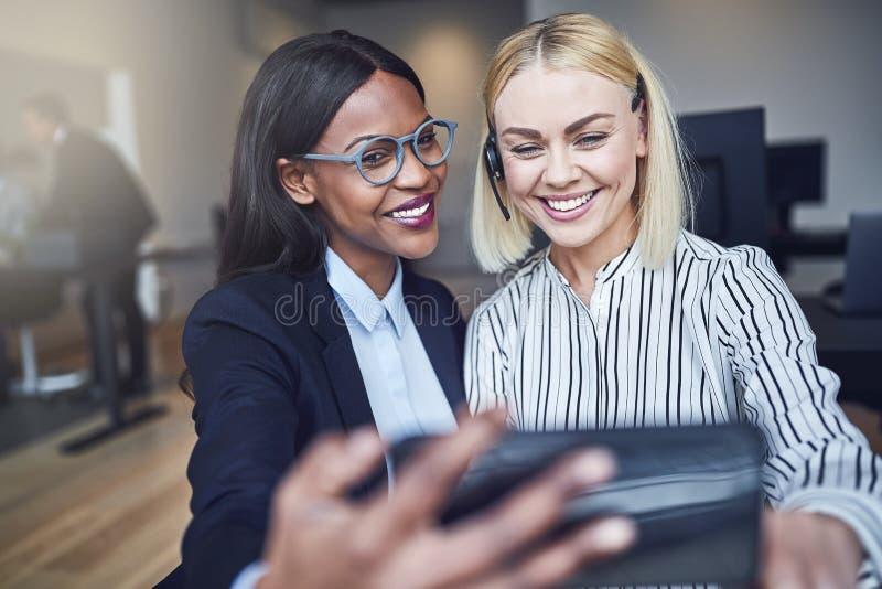 Dwa uśmiechniętego młodego bizneswomanu bierze selfies wpólnie w obraz stock