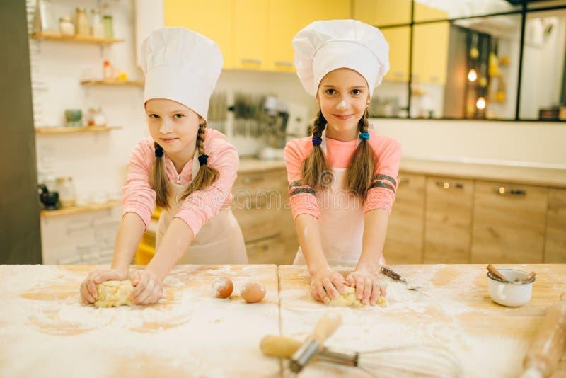 Dwa uśmiechniętego mała dziewczynka kucharza w nakrętkach ma zabawę zdjęcie stock
