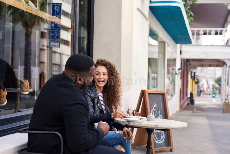 Dwa uśmiechniętego przyjaciela opowiada wpólnie przy chodniczek kawiarnią obraz stock