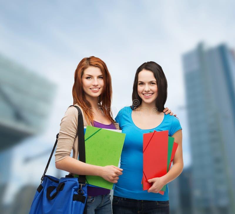 Dwa uśmiechniętego ucznia z torbą i falcówkami fotografia stock