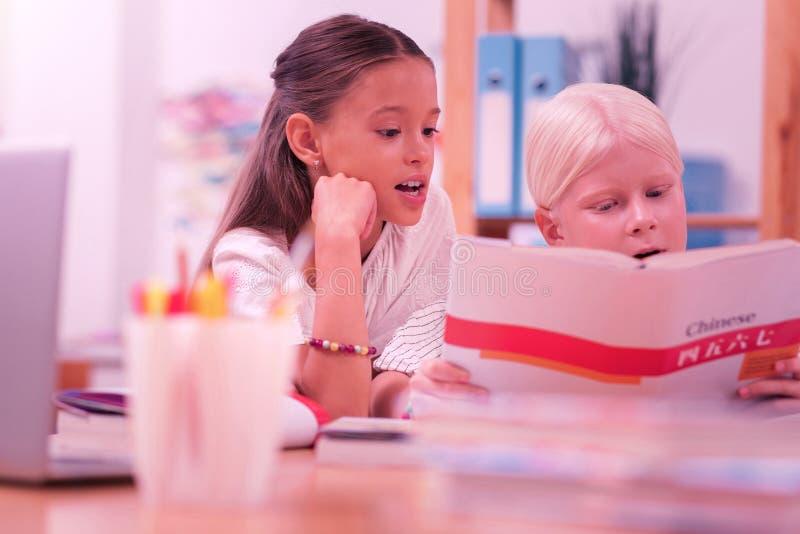 Dwa ucznia czyta chińskiego workbook przy szkołą zdjęcie royalty free