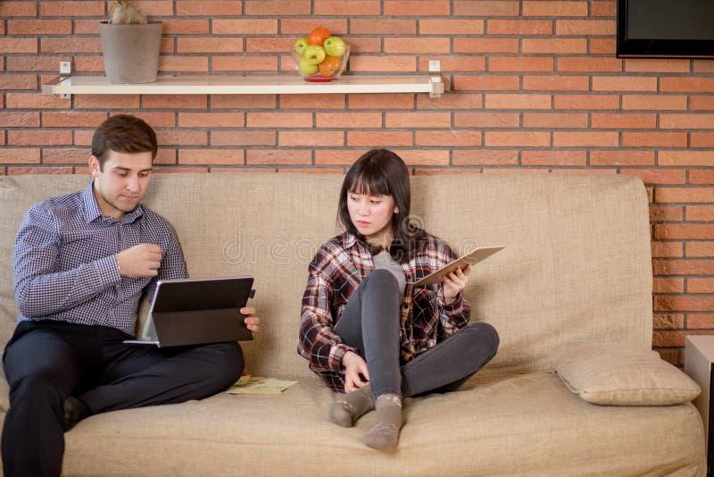 Dwa ucznia przygotowywa dla egzaminów w mieszkania wnętrzu zdjęcia stock