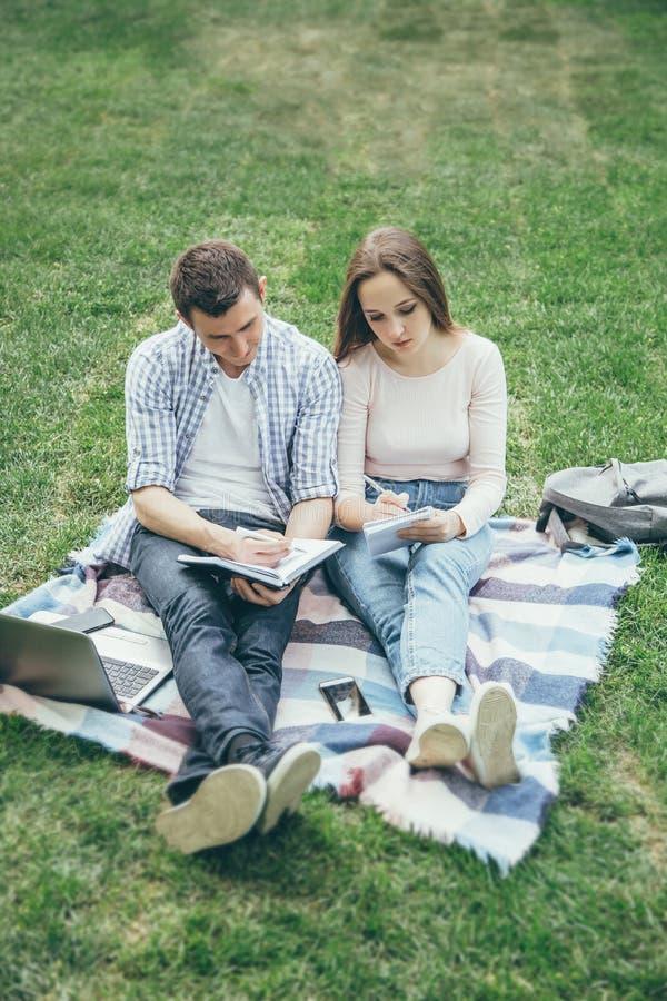 Dwa ucznia przygotowywają dla seminaryjnego obsiadania na trawie edukacja w sieci zdjęcie royalty free