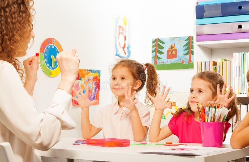 Dwa ucznia robi palców ćwiczeniom jako ich nauczyciel obrazy royalty free