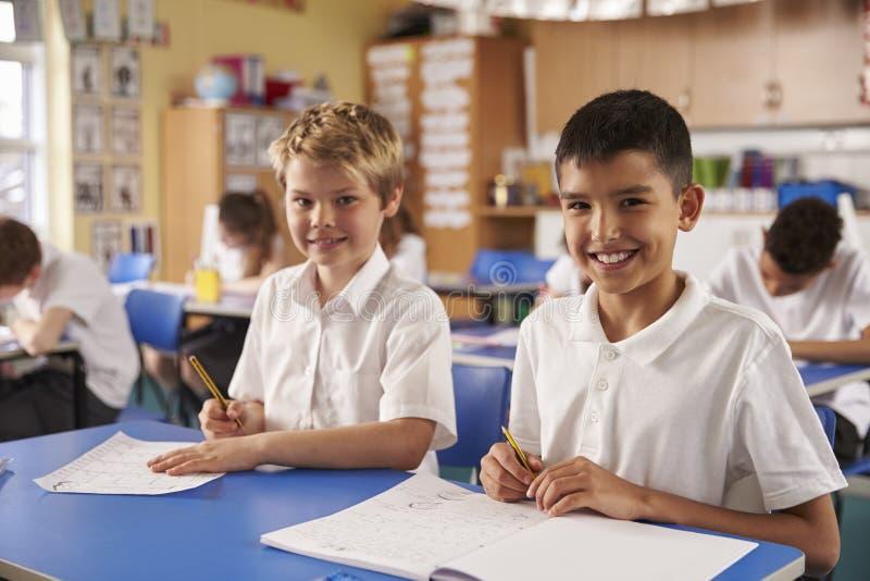 Dwa ucznia w szkoły podstawowej klasie, patrzeje kamera obraz royalty free