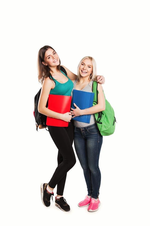 Dwa ucznia z szkolnych toreb pozować odizolowywam dalej zdjęcia royalty free