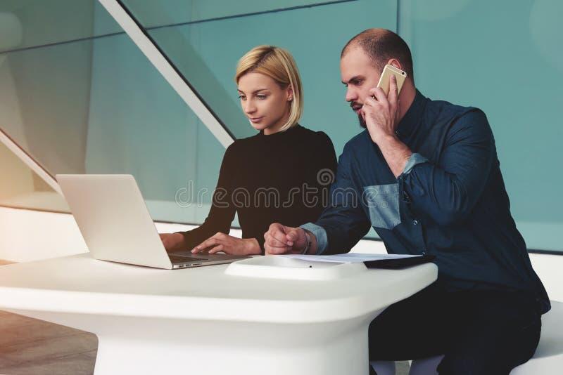 Dwa ufnego biznesowego pracownika używa książki i komórki telefon dla rozwoju wspólny projekt obraz stock