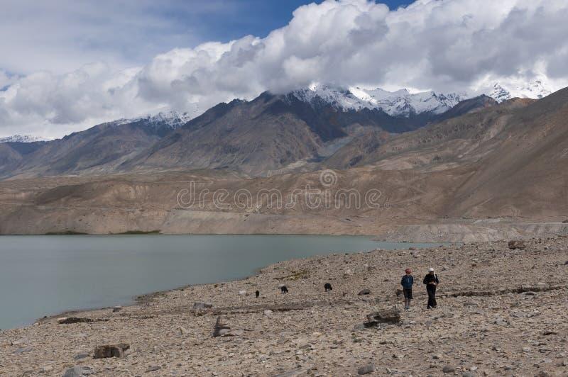 Dwa ujghurzy kobiety chodzi jeziorem z górami na tle wzdłuż Karakoram autostrady w Północno-zachodni Chiny, obraz stock