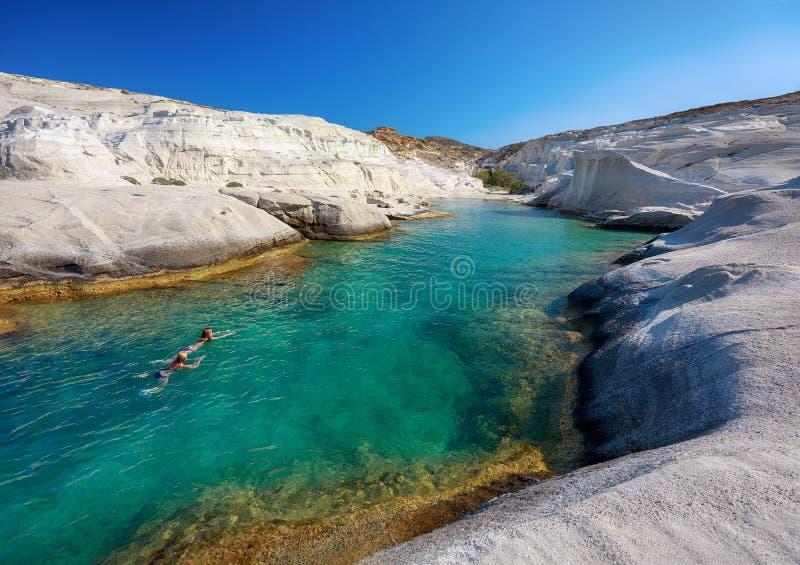 Dwa unidentifiable kobiety pływa w jasnych wodach Sarakiniko zatoka, Milos wyspy, Cyclades, Grecja obrazy royalty free