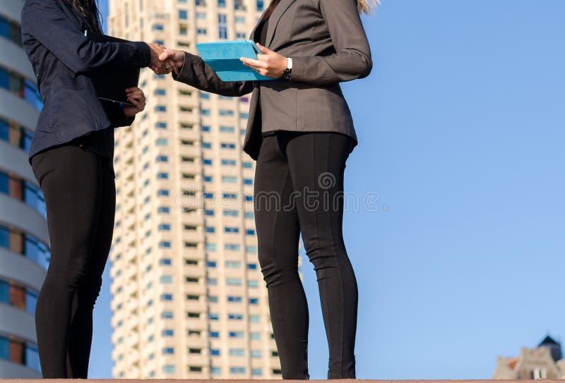 Dwa unidentifiable młodej kobiety trzyma pastylki trząść ręki - biznesowa transakcja obraz royalty free