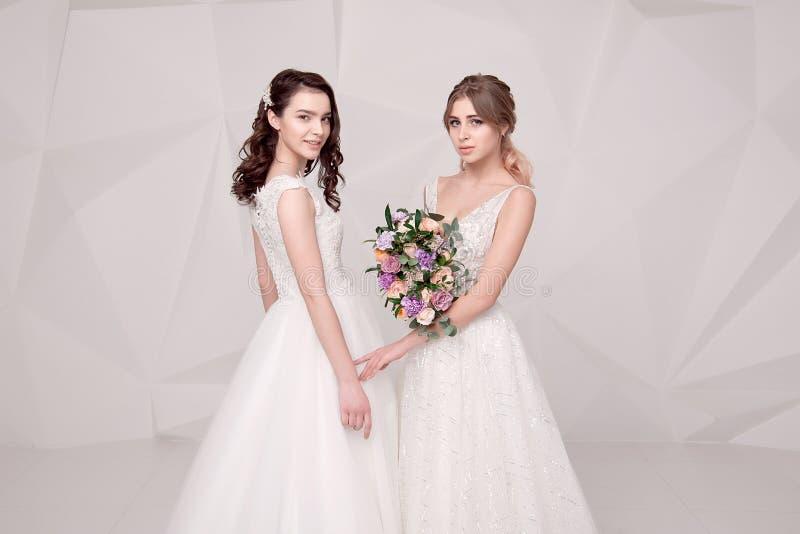 Dwa uroczej damy jest ubranym w długich modnych sukniach trzyma kwiaty fotografia royalty free