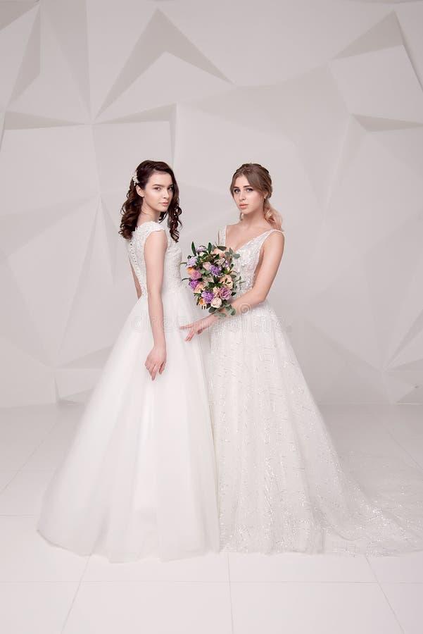 Dwa uroczej damy jest ubranym w długich modnych sukniach trzyma kwiaty zdjęcie stock