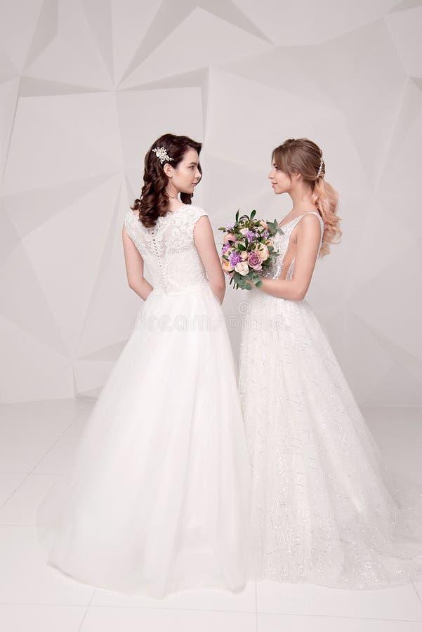 Dwa uroczej damy jest ubranym w długich modnych sukniach trzyma kwiaty obrazy royalty free