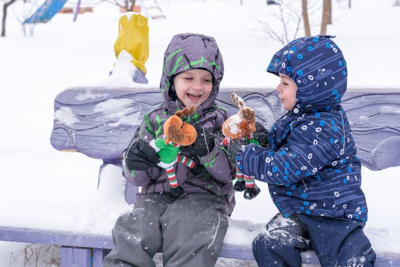 Dwa uroczej preschool dzieciaków brata chłopiec w zimy odzieży siedzą amou zdjęcia stock