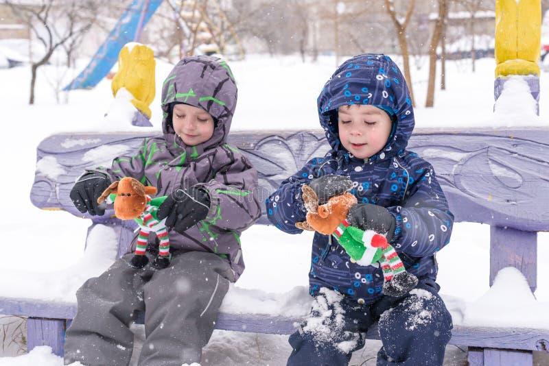 Dwa uroczej preschool dzieciaków brata chłopiec w zimy odzieży siedzą amou obrazy royalty free