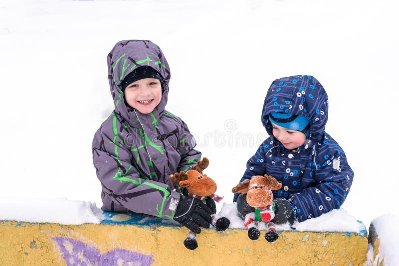 Dwa uroczej preschool dzieciaków brata chłopiec w zimy odzieży siedzą amou obrazy stock
