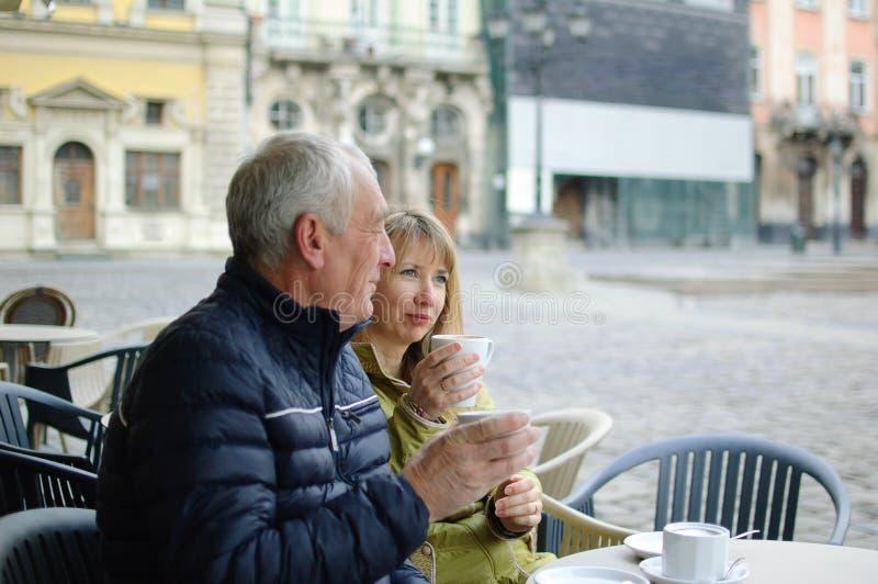 Dwa w ?rednim wieku turysty pije kaw? w kawiarni z tarasem outdoors w antycznym mie?cie w ranku podczas wcze?nie obrazy royalty free