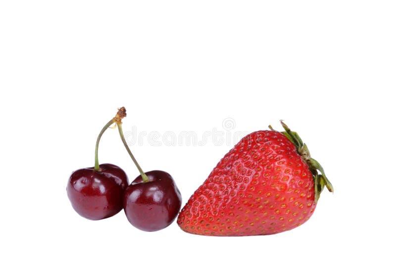 Dwa wiśnia i odosobniona truskawka - obrazy stock