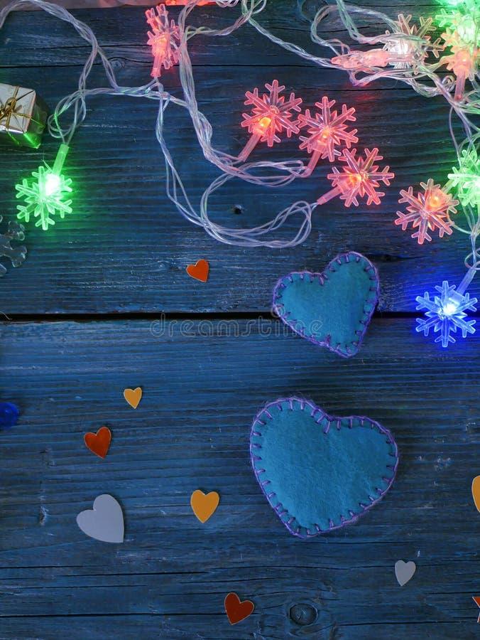 Dwa wielkiego handmade odczuwanego serca i few małych ones robić barwiony papier, choinki płatek śniegu na błękitnej teksturze gi zdjęcia stock
