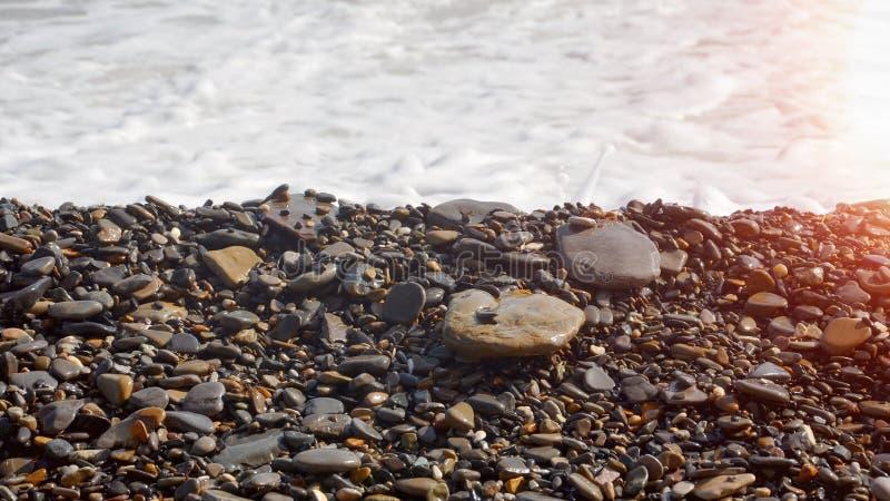Dwa wielkiego kamienia i małych otoczaki na tle morze pienią się obraz stock