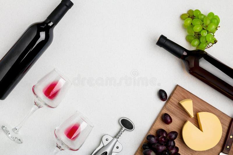 Dwa wina szkła z czerwonym winem, butelką czerwone wino i serem na białym tle, Horyzontalny widok od wierzchołka fotografia stock