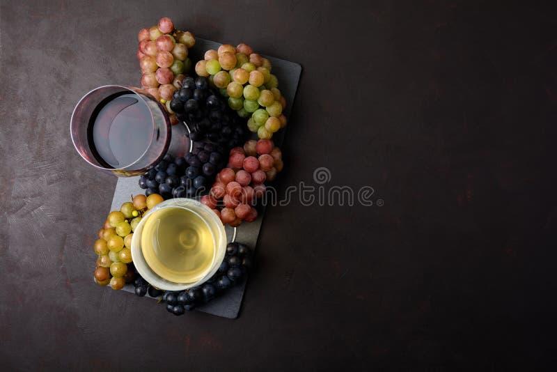 Dwa wineglasses z winem, butelkami i winogronami na ciemnym drewnianym tle czerwonym i białym, zdjęcie stock