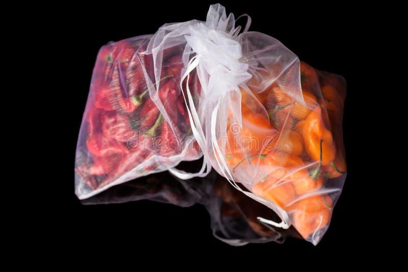 Dwa worka z pomarańczowymi i czerwonymi pieprzami obraz stock