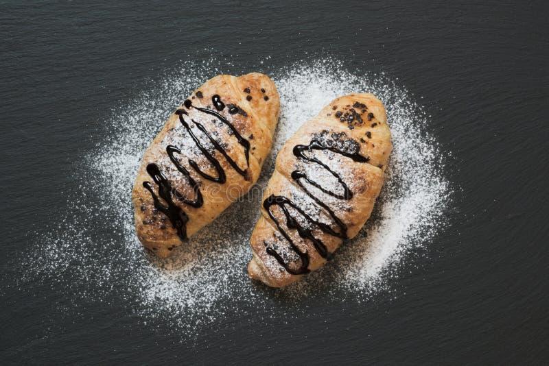 Dwa wyśmienicie świeżo piec croissants na łupkowym tle Odgórny widok śniadanie fotografia royalty free