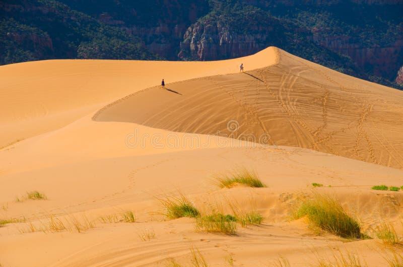 Dwa wycieczkowicza chodzą obręcz wysokie piasek diuny w Utah zdjęcie stock