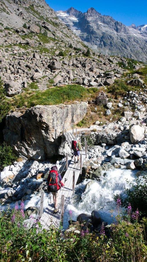 Dwa wycieczkowicza krzyżują zatoczkę nad małym drewnianym mostem w Francuskich Alps obraz royalty free