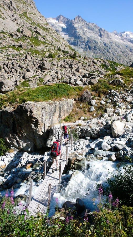 Dwa wycieczkowicza krzyżują zatoczkę nad małym drewnianym mostem w Francuskich Alps zdjęcie stock