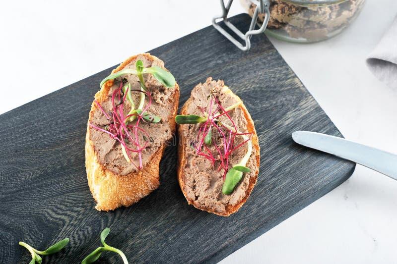 Dwa wznosząca toast kanapka grzanka z łbem i zieleniami fotografia stock
