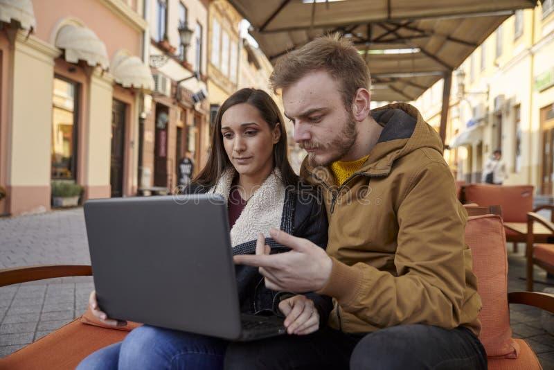 Dwa Yong ludzie, 20-29 lat, działanie, patrzejący laptop, siedzi w kawiarni zdjęcia royalty free