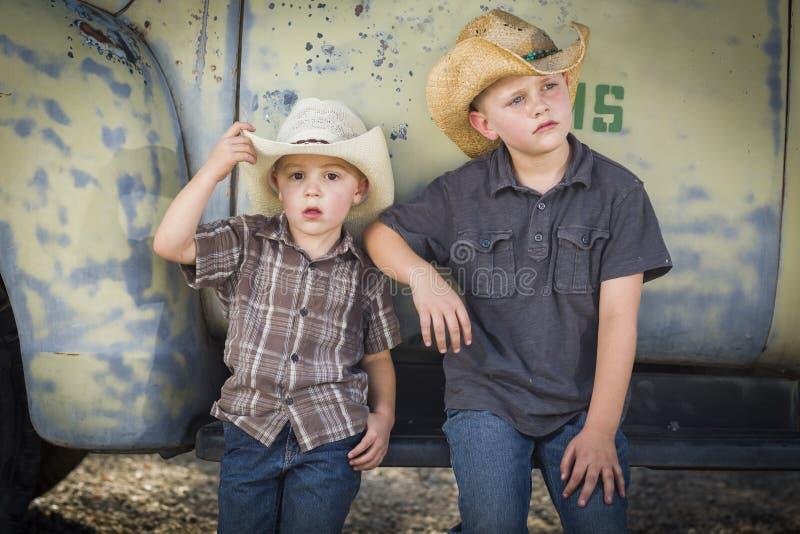 Dwa Young Boys Jest ubranym kowbojskich kapelusze Opiera Przeciw antyk ciężarówce obraz stock