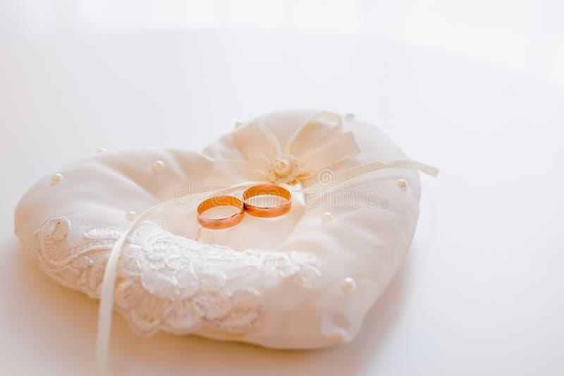 Dwa złocistej szerokiej obrączki ślubnej na białej dekoracyjnej poduszce dekorowali z biel koralikami na lekkim tle i koronką obraz stock