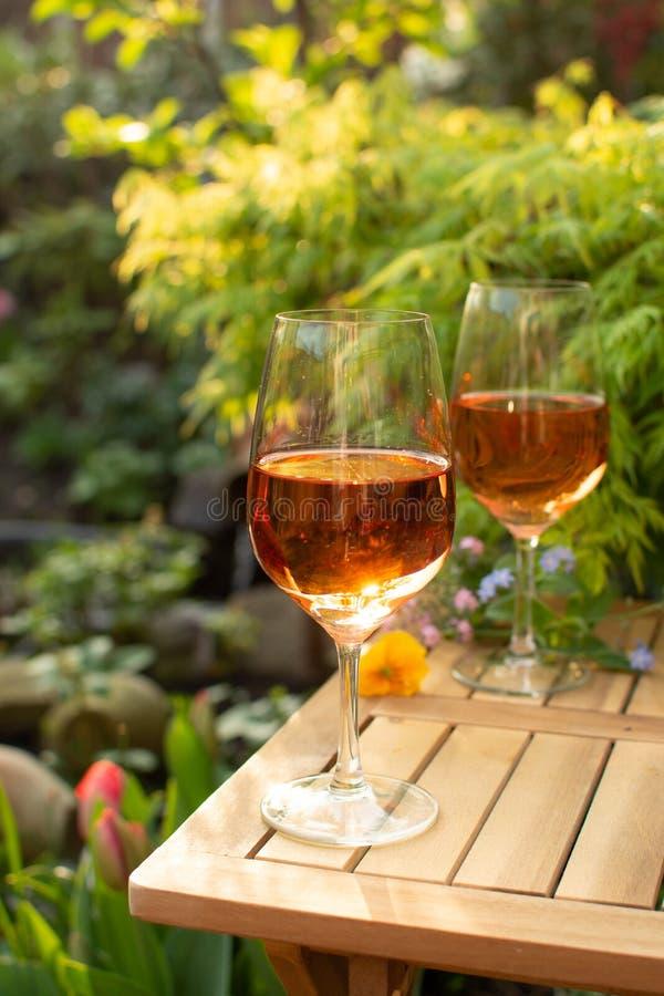 Dwa zimna wina różanego szkła słuzyć na plenerowym tarasie w ogródzie w zdjęcie royalty free
