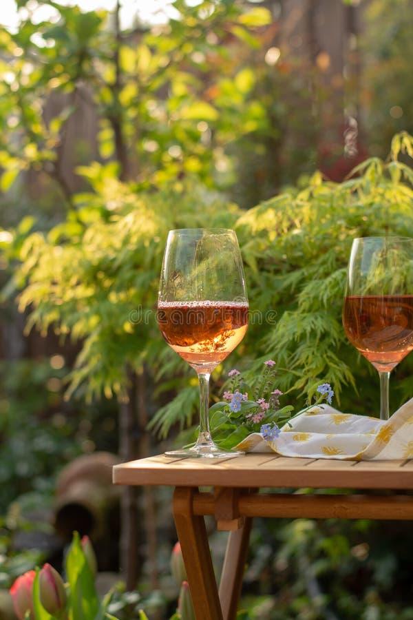 Dwa zimna wina różanego szkła słuzyć na plenerowym tarasie w ogródzie w fotografia royalty free