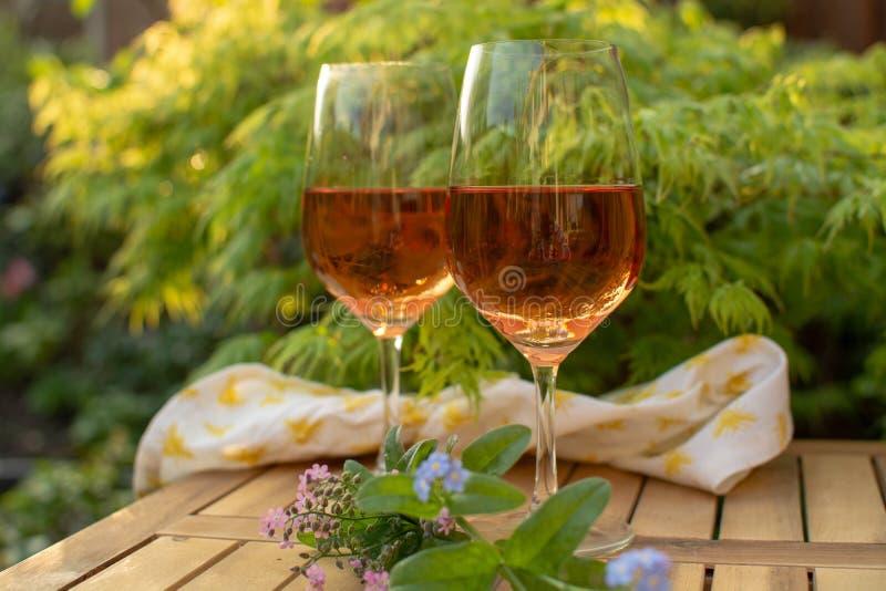 Dwa zimna wina różanego szkła słuzyć na plenerowym tarasie w ogródzie w zdjęcie stock