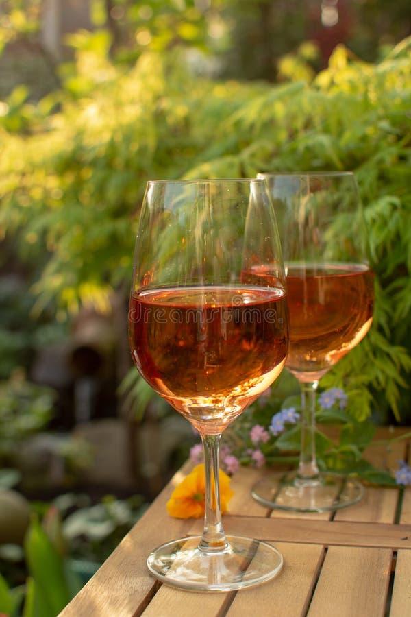 Dwa zimna wina różanego szkła słuzyć na plenerowym tarasie w ogródzie w zdjęcia royalty free