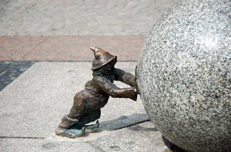 Dwarf pushing stone ball Wroclaw Poland royalty free stock image