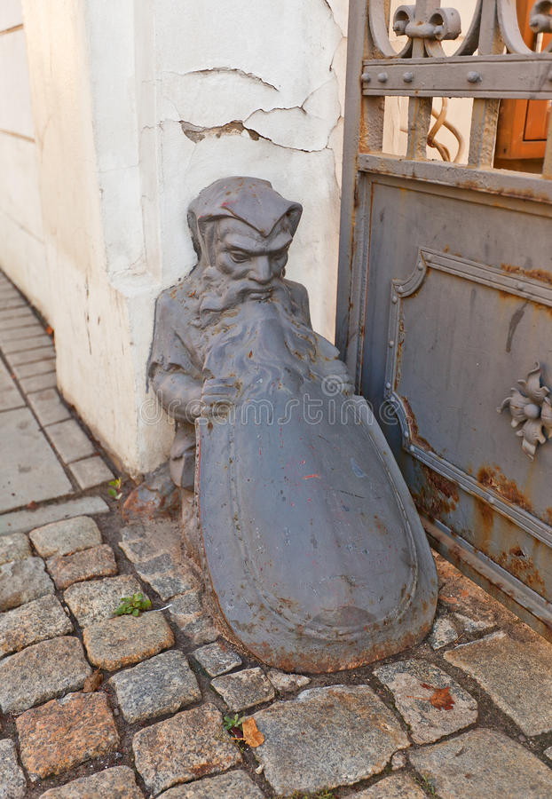 Dwarf shape old wheel guard (bollard) in Lodz, Poland. Old wheel guard (bollard) in the shape of dwarf with a shield near historic house (XIX c.) in Lodz, Poland stock images