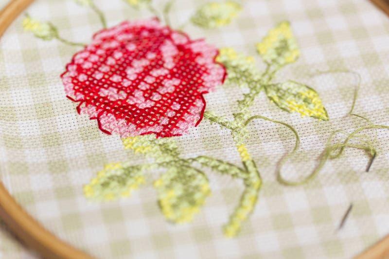Dwars-steekborduurwerk op rode hoepels - nam met groene bladeren toe stock afbeeldingen