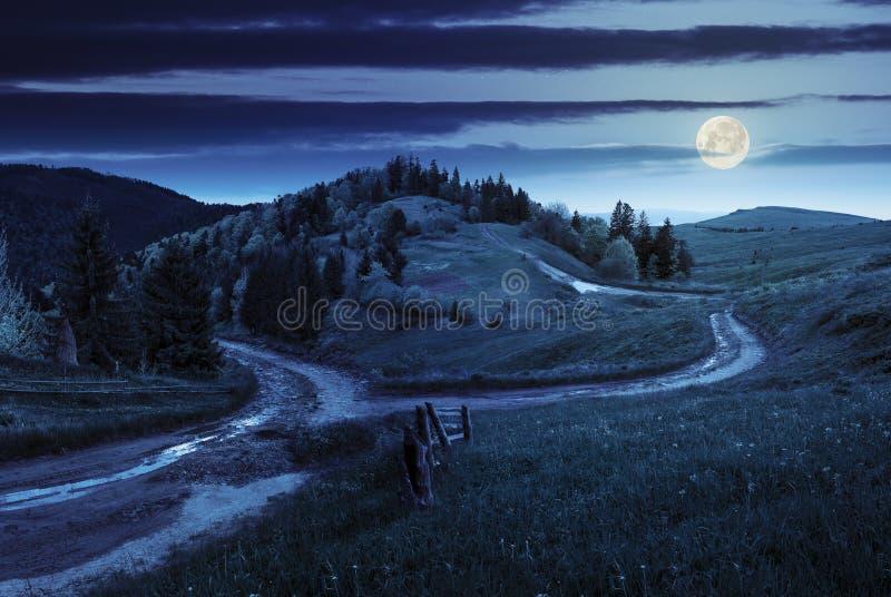Dwarsweg op hellingsweide in berg bij nacht stock fotografie