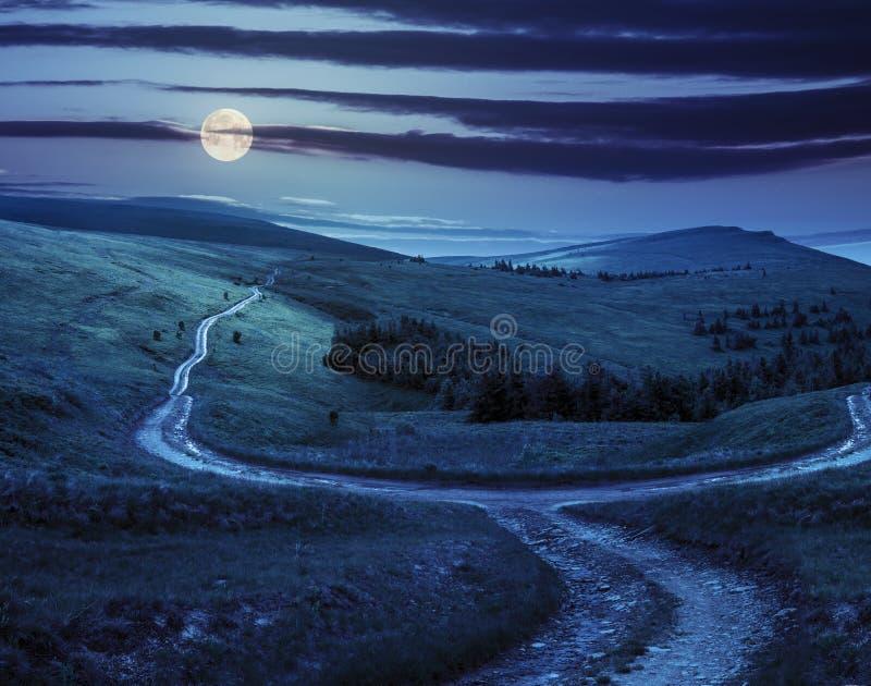 Dwarsweg op hellingsweide in berg bij zonsopgang bij nacht stock foto