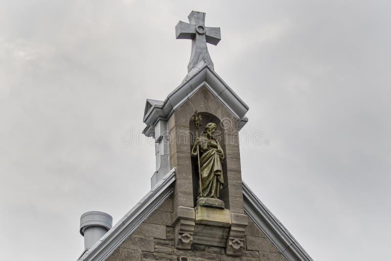 Dwarszitting bovenop kerktorenspits stock foto