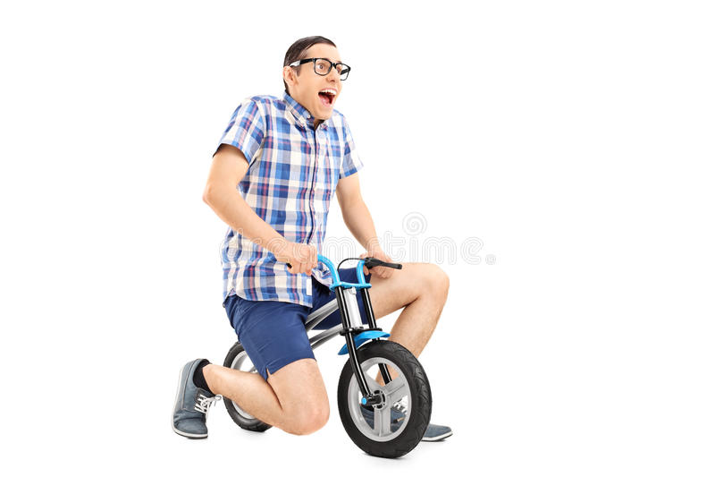Dwaze jonge kerel die een uiterst kleine fiets berijden stock foto's