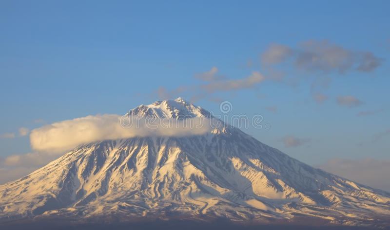 The dwelling of demigods - Olympe. Volcano in a half ring of clouds. Are well visible barranco. Kamchatka royalty free stock images