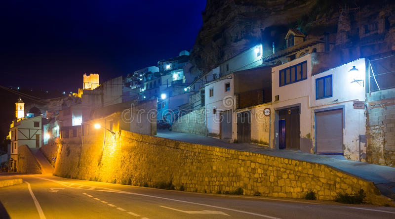 Dwelling houses into rock in evening. Alcala del Jucar. Street at town with dwelling houses into rock in evening. Alcala del Jucar. Castile-La Mancha, Spain royalty free stock image