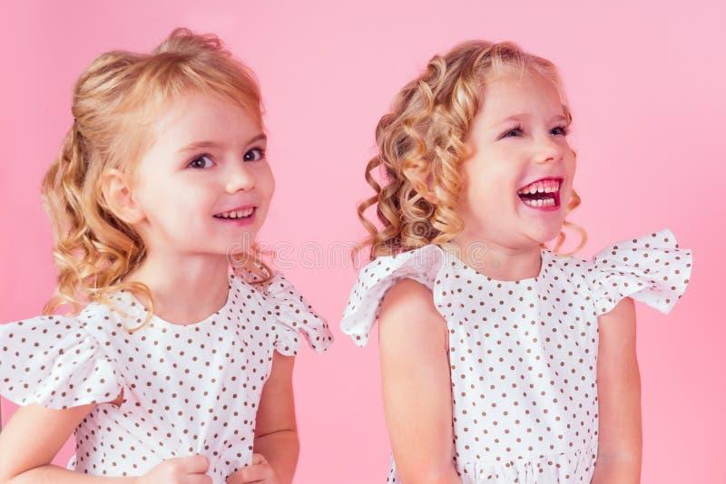 Dwie dziewczynki, piękne, niebieskie oczy, skalują blond włosy z koronką tiary na głowie w słodkiej białej sukience w fotografia stock